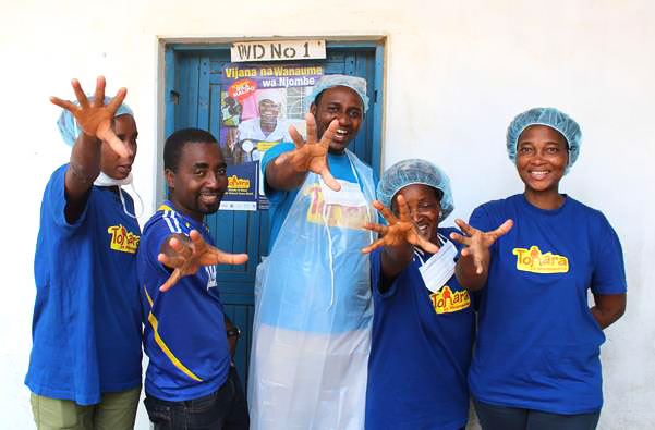 Njombe, Tanzania—VMMC providers at Itulahumba Dispensary give a high five to celebrate the 500,000 VMMC milestone.